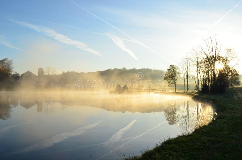 Lever de soleil brumeux de matin au-dessus d'un lac avec le pont photo libre de droits