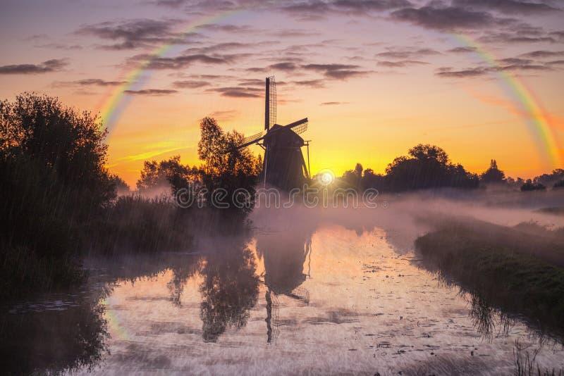 Lever de soleil chaud de moulin à vent brumeux et pluvieux images stock