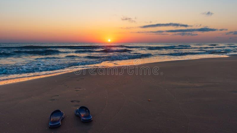 Lever de soleil coloré étonnant en mer, empreintes de pas dans le sable image stock