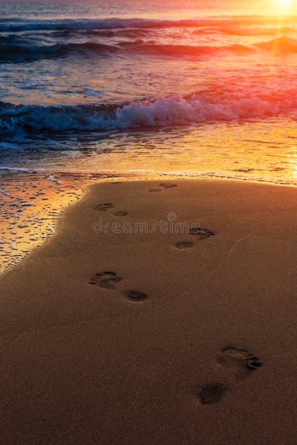 Lever de soleil coloré étonnant en mer, empreintes de pas dans le sable image libre de droits