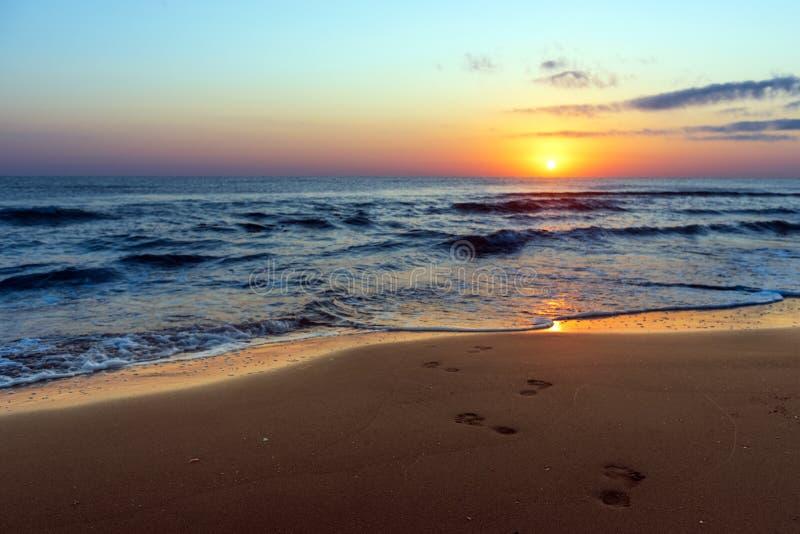 Lever de soleil coloré étonnant en mer, empreintes de pas dans le sable photographie stock
