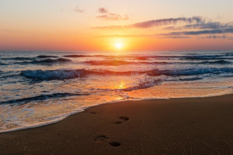 Lever de soleil coloré étonnant en mer, empreintes de pas dans le sable photos stock