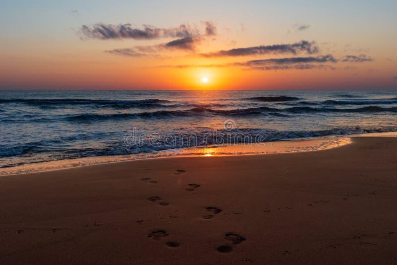 Lever de soleil coloré étonnant en mer, empreintes de pas dans le sable photos libres de droits
