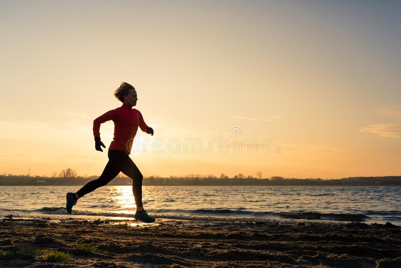 Lever de soleil courant de silhouette de plage de femme, littoral de lac photo libre de droits