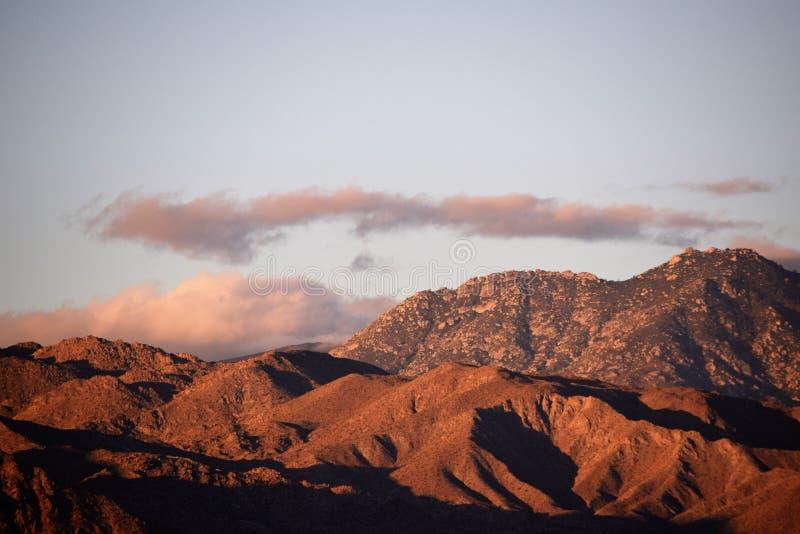 Lever de soleil de désert avec les nuages pourpres images stock