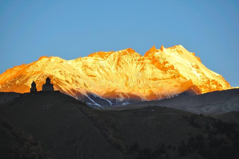 Lever de soleil d'église de trinité sainte, Kazbegi, la Géorgie photos stock