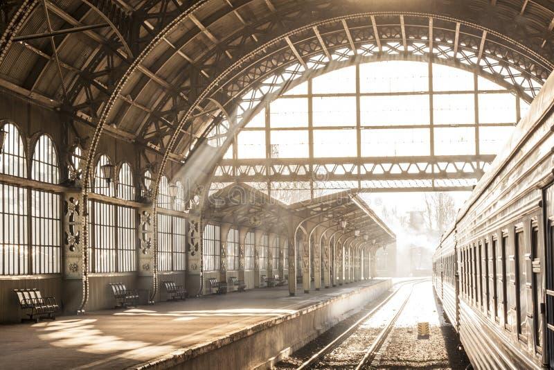 Lever de soleil d'intérieur de coucher du soleil de station de train dans la sépia Chariot et plate-forme avec le toit de constru photo libre de droits