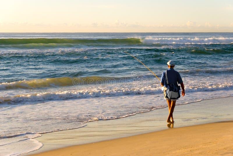 Lever de soleil de vague déferlante de pêcheur de plage photo libre de droits