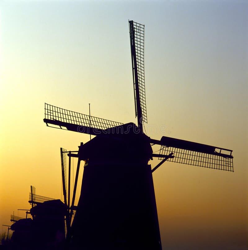 Lever de soleil derrière un groupe de moulins à vent néerlandais traditionnels image stock