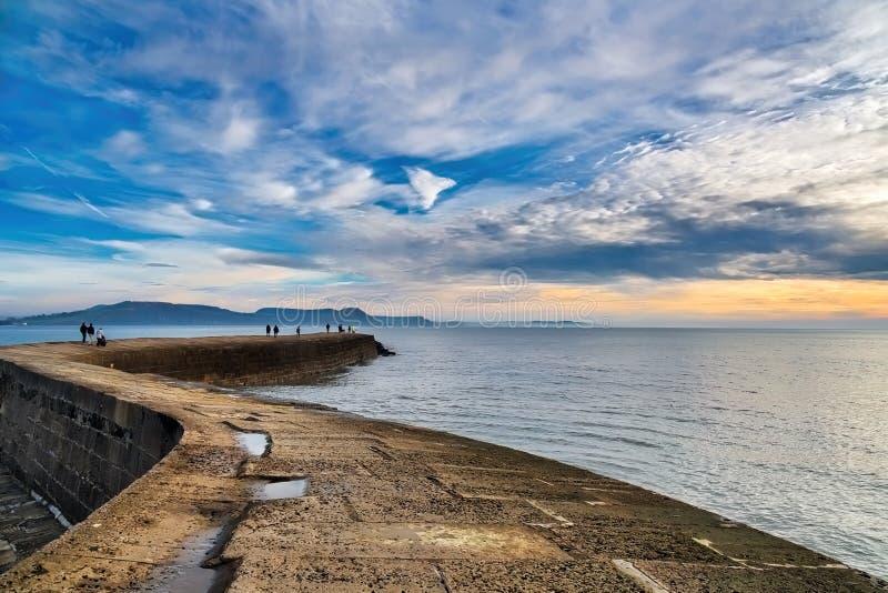 Lever de soleil dramatique d'hiver au-dessus du mur de port de Cobb photographie stock libre de droits