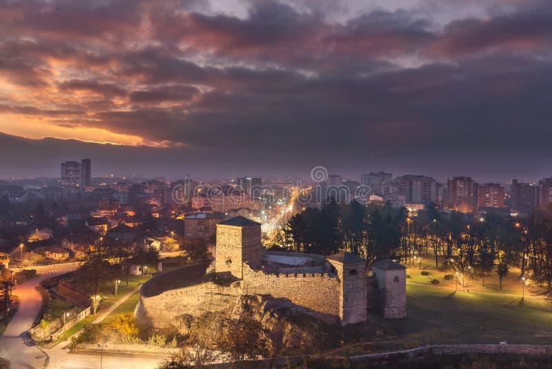 Lever de soleil dramatique de matin au-dessus de ville somnolente et de forteresse antique de premier plan image libre de droits