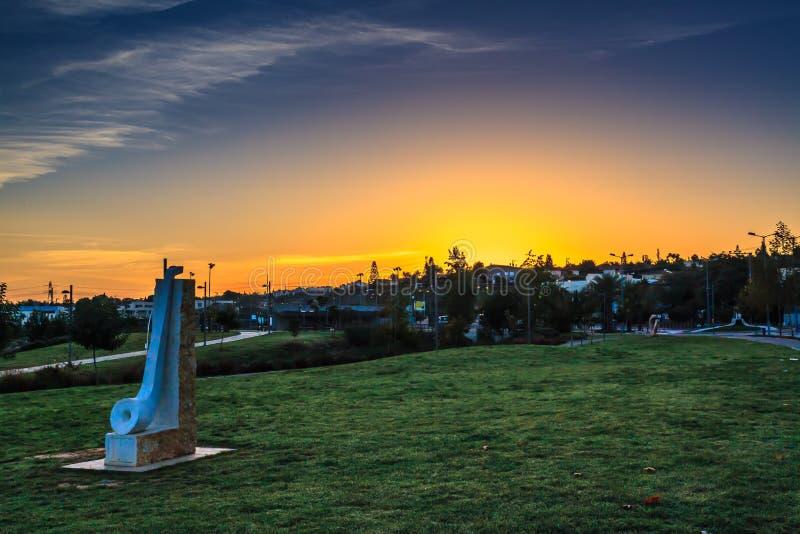 Lever de soleil en parc de ville avec la statue en pierre photo stock
