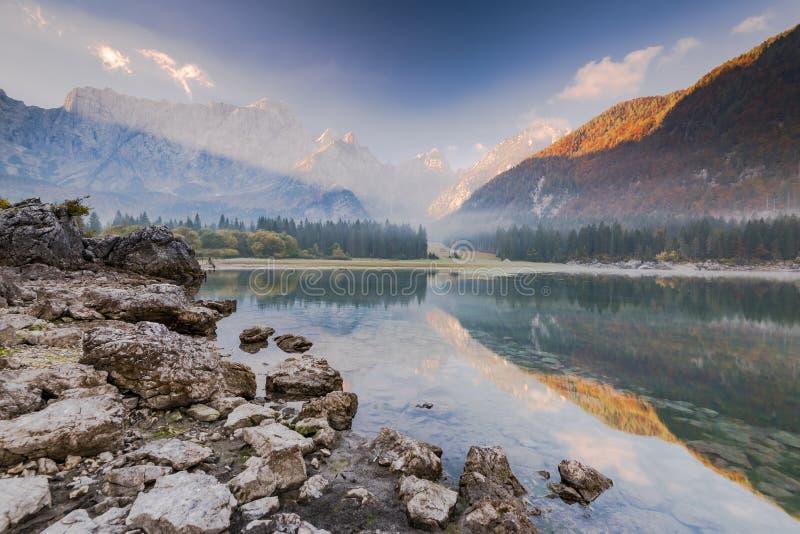 Lever de soleil froid et brumeux au-dessus des lacs Fusine en Italie image libre de droits