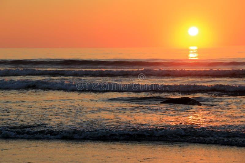 Lever de soleil magnifique au-dessus des roches le long du rivage image stock