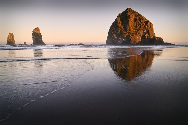 Lever de soleil de roche de meule de foin, plage de canon, Orégon photo libre de droits