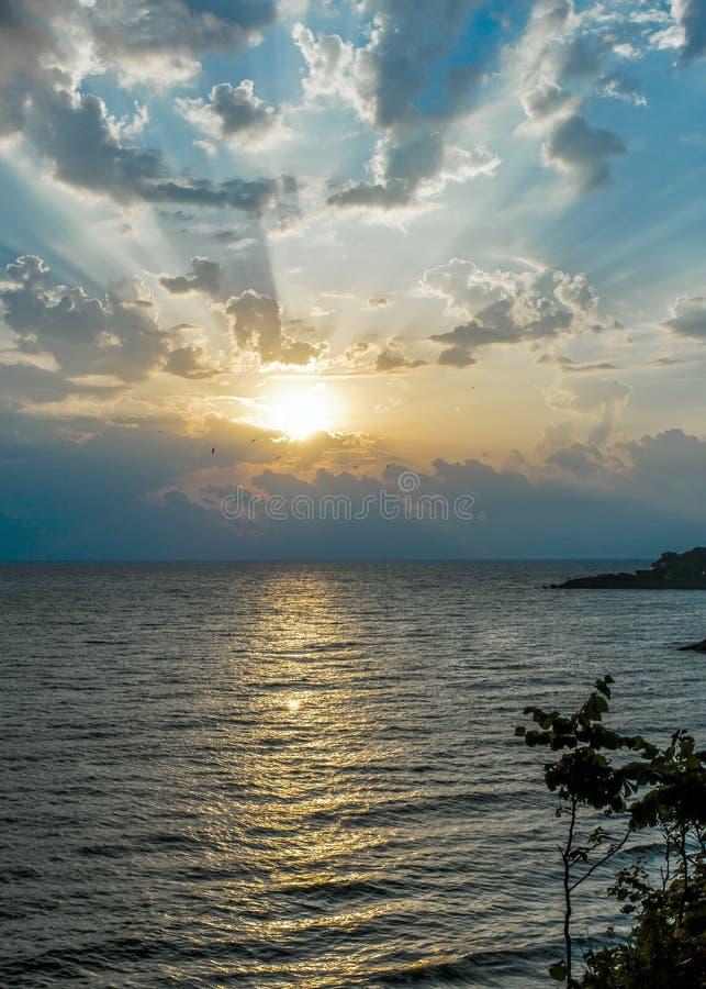 Lever de soleil stupéfiant et vagues de mer et nuages et mouettes puissants photos stock