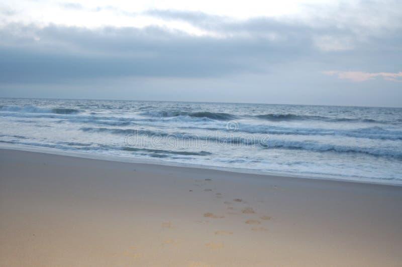 Lever de soleil sur l'océan, le ciel blanc, et le sable photographie stock libre de droits