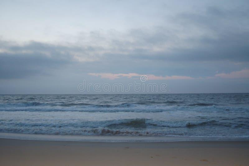 Lever de soleil sur l'océan, le ciel blanc, et le sable photos libres de droits