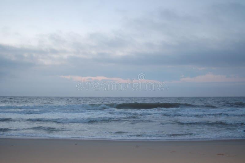 Lever de soleil sur l'océan, le ciel blanc, et le sable image stock