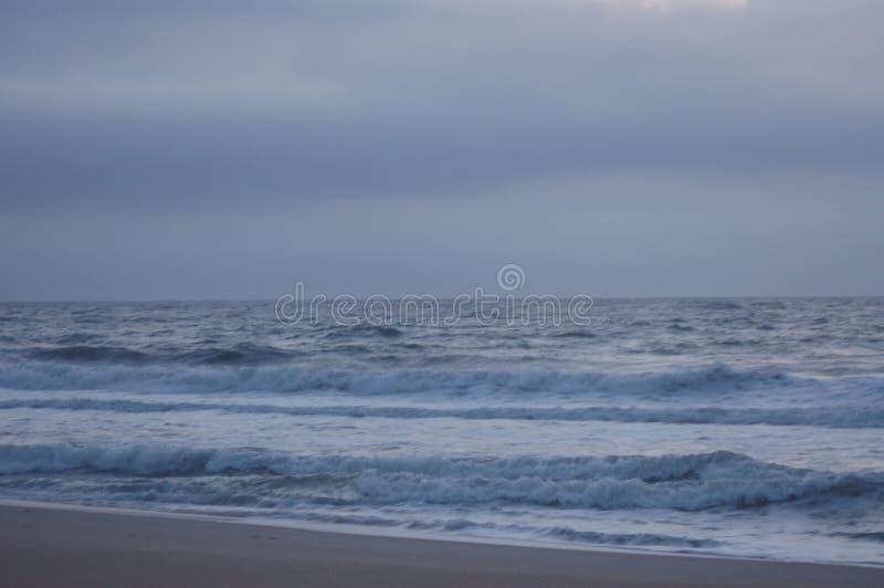 Lever de soleil sur l'océan, le ciel blanc, et le sable photos stock