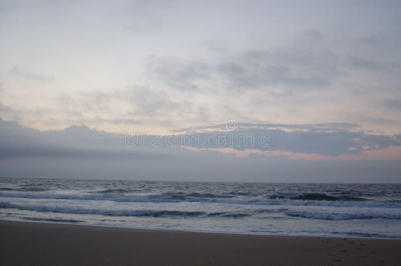 Lever de soleil sur l'océan, le ciel blanc, et le sable images libres de droits