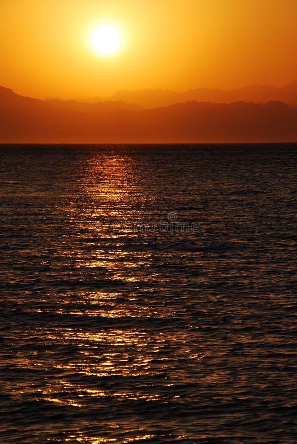 Lever de soleil sur la mer avec des montagnes hautes photographie stock libre de droits