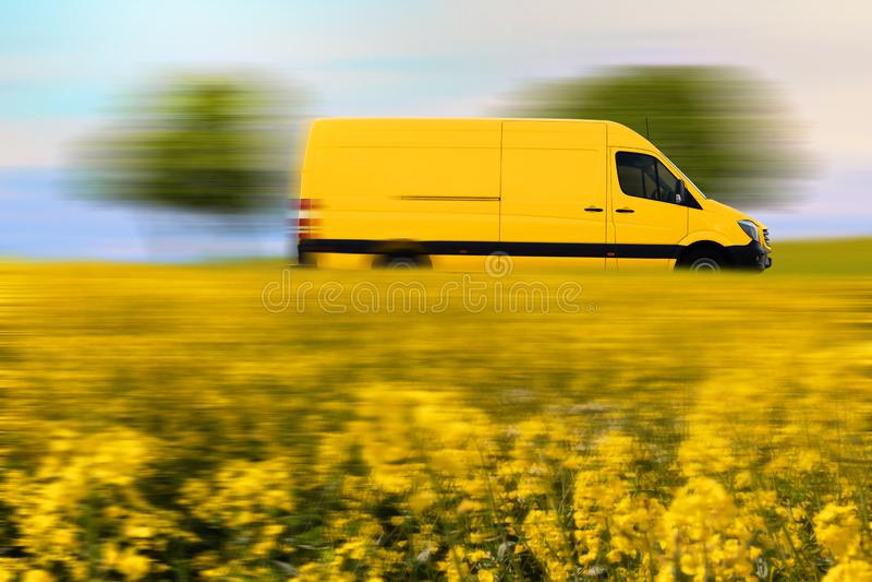 Leverans för snabb jordlott, gul postskåpbil på landsvägen royaltyfri foto