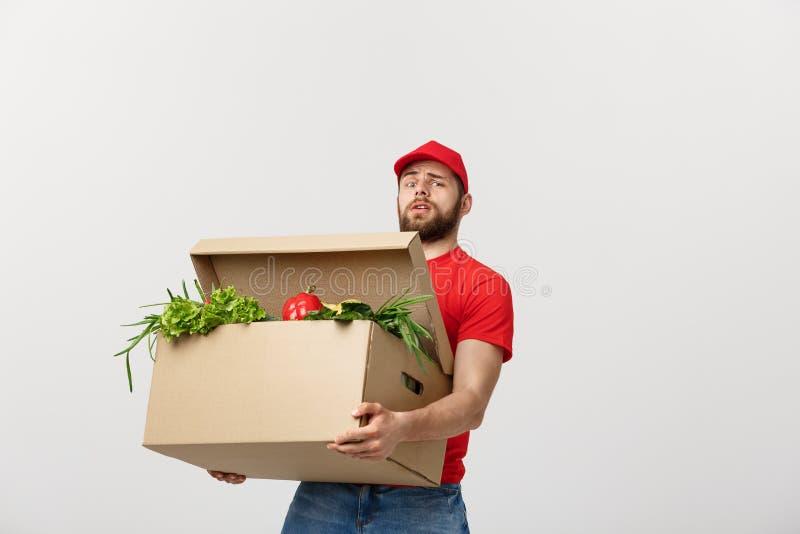 Leveransbegrepp: Den stiliga leveransmannen rymmer en tung livsmedelsbutikask isolerad över grå bakgrund arkivfoto