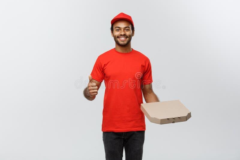 Leveransbegrepp - ståenden av den lyckliga afrikansk amerikanleveransmannen som rymmer en pizzaaskpacke och visar, dunkar upp arkivfoton
