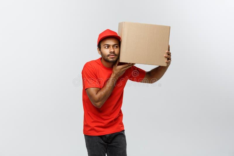 Leveransbegrepp - ståenden av den nyfikna afrikansk amerikanleveransmannen lyssnar inom en askpacke Isolerat på grå färg arkivbilder