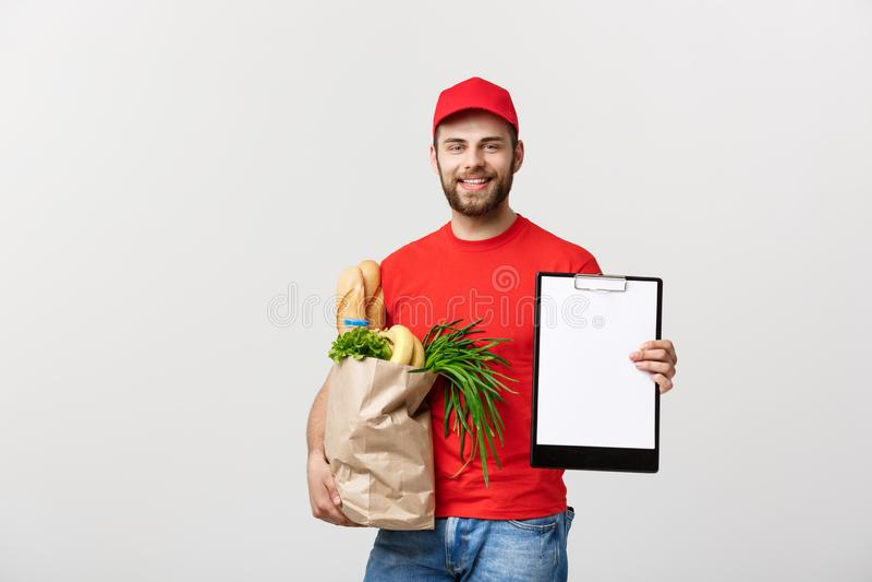 Leveransbegrepp: Stilig Caucasian man f?r livsmedelsbutikleveranskurir i r?d likformig med livsmedelsbutikasken med ny frukt och royaltyfria bilder