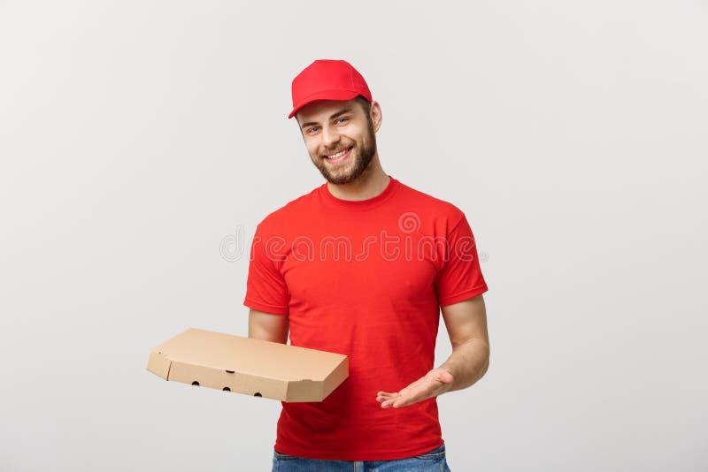 Leveransbegrepp: Unga haapy caucasian stiliga askar för pizza för pizzaleveransman som hållande isoleras över grå bakgrund royaltyfri bild