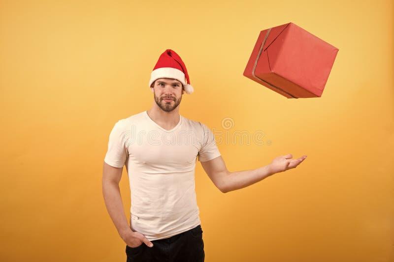 Leveransjulg?vor lycklig santa man p? gul bakgrund Morgonen f?r Xmas man i jul f?r santa hatth?ll royaltyfri foto