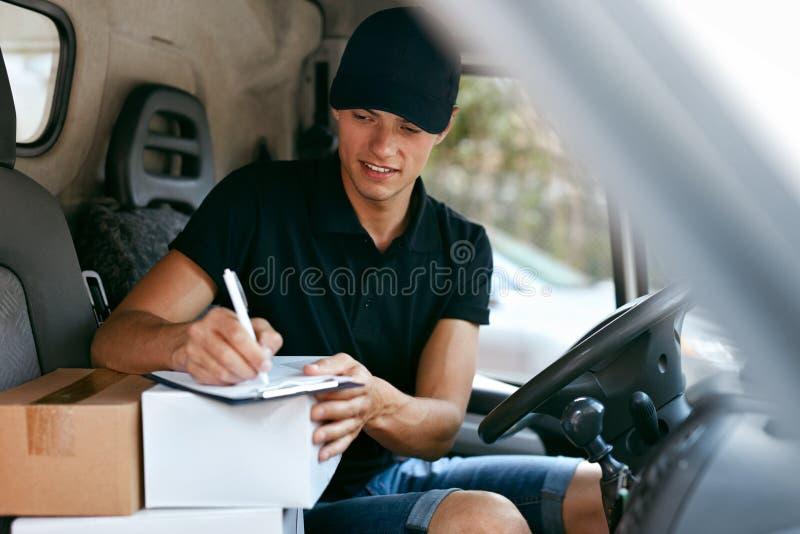 LeveranskurirIn Car With askar Man som levererar att förpacka arkivfoto