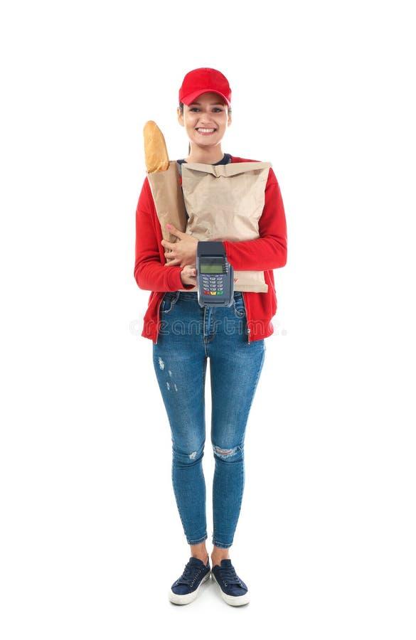 Leveranskvinna som rymmer papperspåsen med mat- och betalningterminalen på vit bakgrund royaltyfri foto