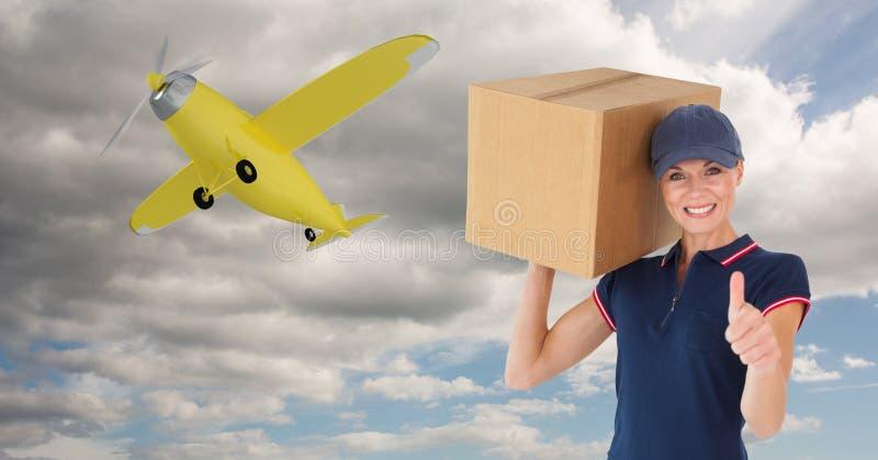 Leveranskvinnavisningen tummar upp, medan bära jordlotten mot flygplanflyg i himmel arkivbild