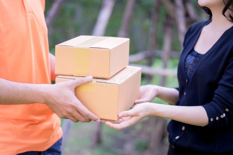 Leveransman i apelsin som räcker packar till en kvinna royaltyfri foto