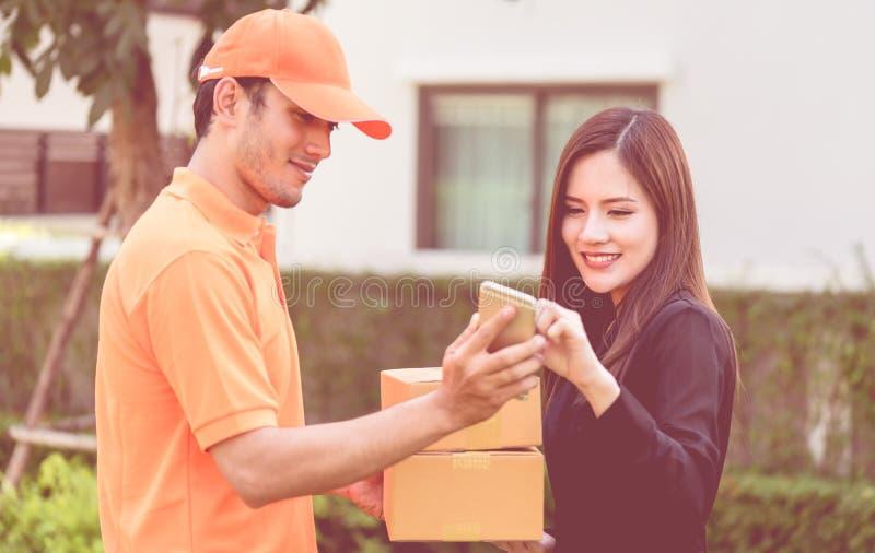 Leveransman i apelsin som räcker packar till en kvinna arkivfoton