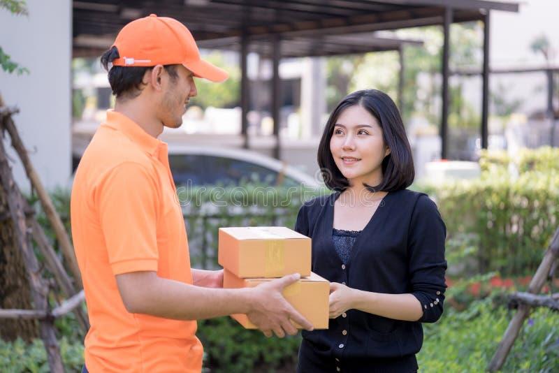 Leveransman i apelsin som räcker packar till en kvinna fotografering för bildbyråer