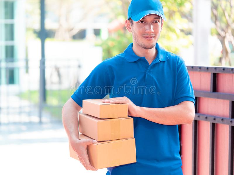 Leveransman i blått som räcker packar arkivfoton