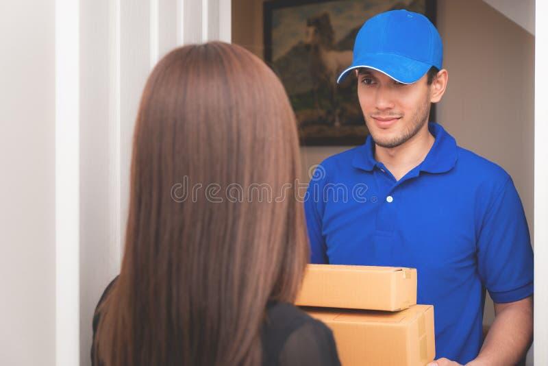 Leveransman i blått som räcker packar till en kvinnadörr royaltyfri bild