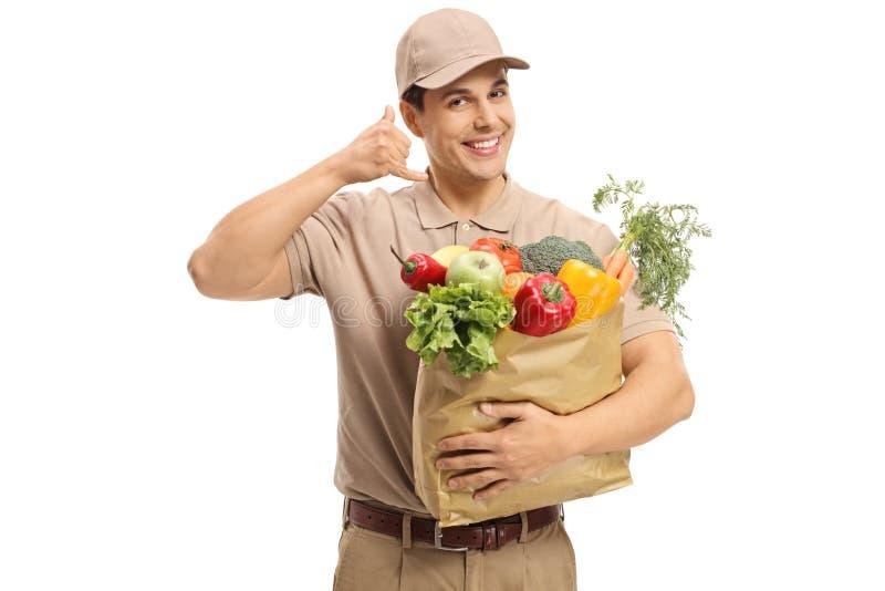 Leveransman med en påse av livsmedel som gör en appell mig gest royaltyfria foton