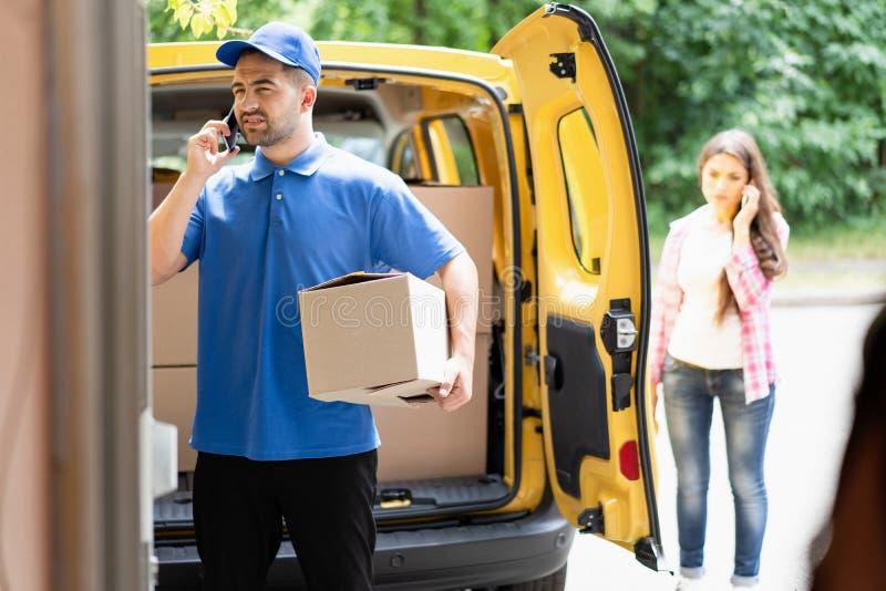 Leveransman som bär den blåa likformiginnehavkartongen och talar på telefonen Öppna skåpbilen i bakgrund fotografering för bildbyråer