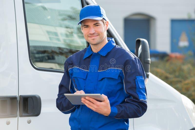 Leveransman som ler genom att använda den Digital minnestavlan med lastbilen royaltyfri bild