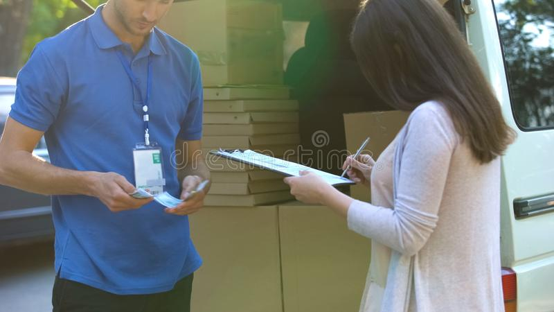 Leveransman som räknar pengar medan undertecknande form för kvinnlig klient om att motta royaltyfria foton