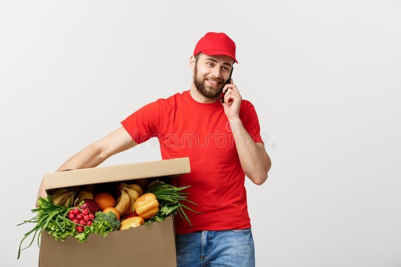 Leveransman som rymmer den pappers- asken med mat och gör en appell med mobiltelefonen som isoleras över grå bakgrund arkivfoton