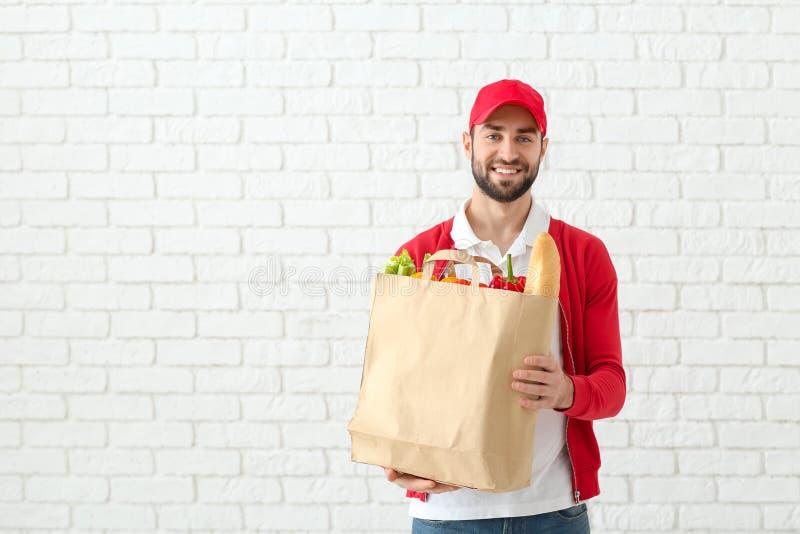 Leveransman som rymmer papperspåsen med mat på bakgrund för tegelstenvägg royaltyfri foto