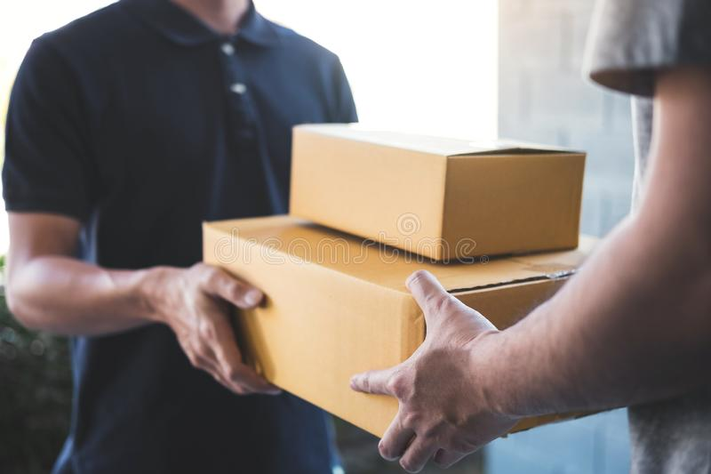 Leveranspostman som ger jordlottasken till mottagaren, ungt acceptera för ägare av kartongpacken från stolpesändning, hem royaltyfri bild