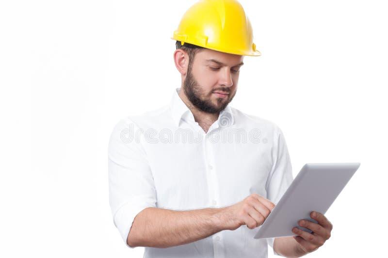 Leverantör i den gula byggmästarehjälmen som arbetar på ett projekt med minnestavlan arkivbild