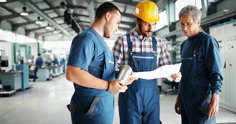 Leverantör med teknikern som kontrollerar på produktion i fabrik royaltyfri bild